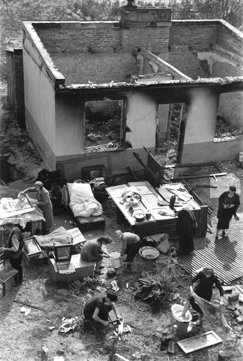 Skutki niemieckich bombardowań Rodzina przed swoim zniszczonym domem próbuje wykonywać zwyczajne, codzienne czynności. Fotografia Juliena Bryana.